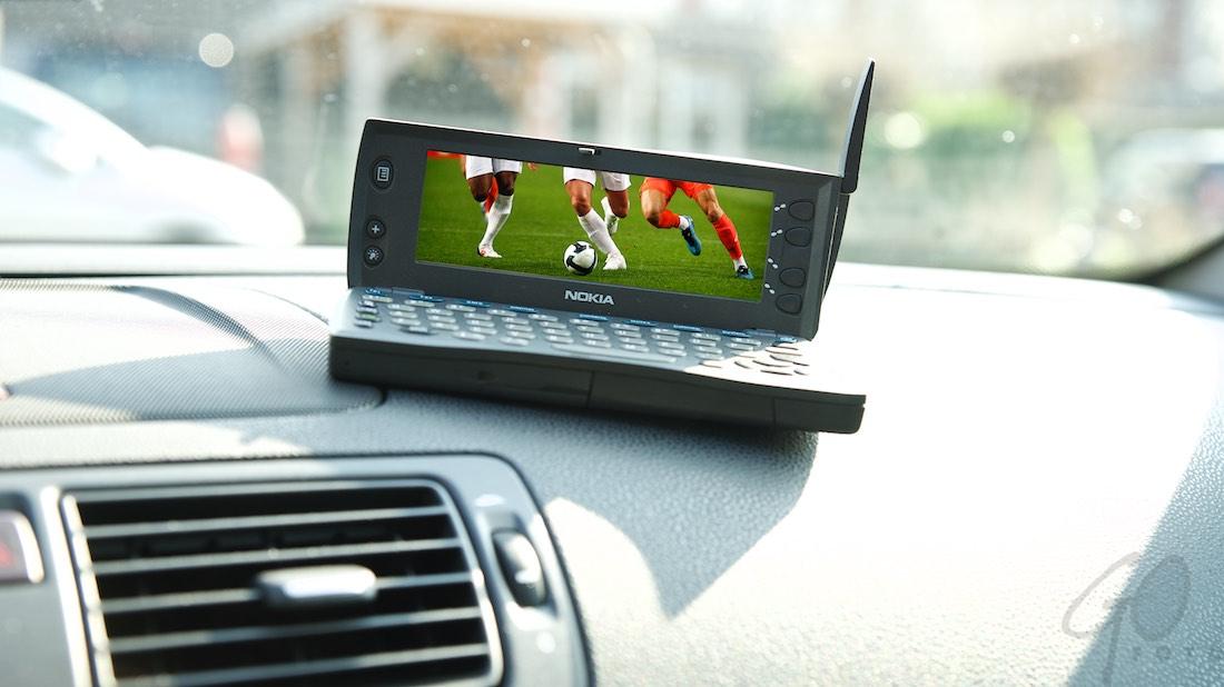 Mobiel is de nieuwe kabel. Oude smartphone op dashboard van auto.