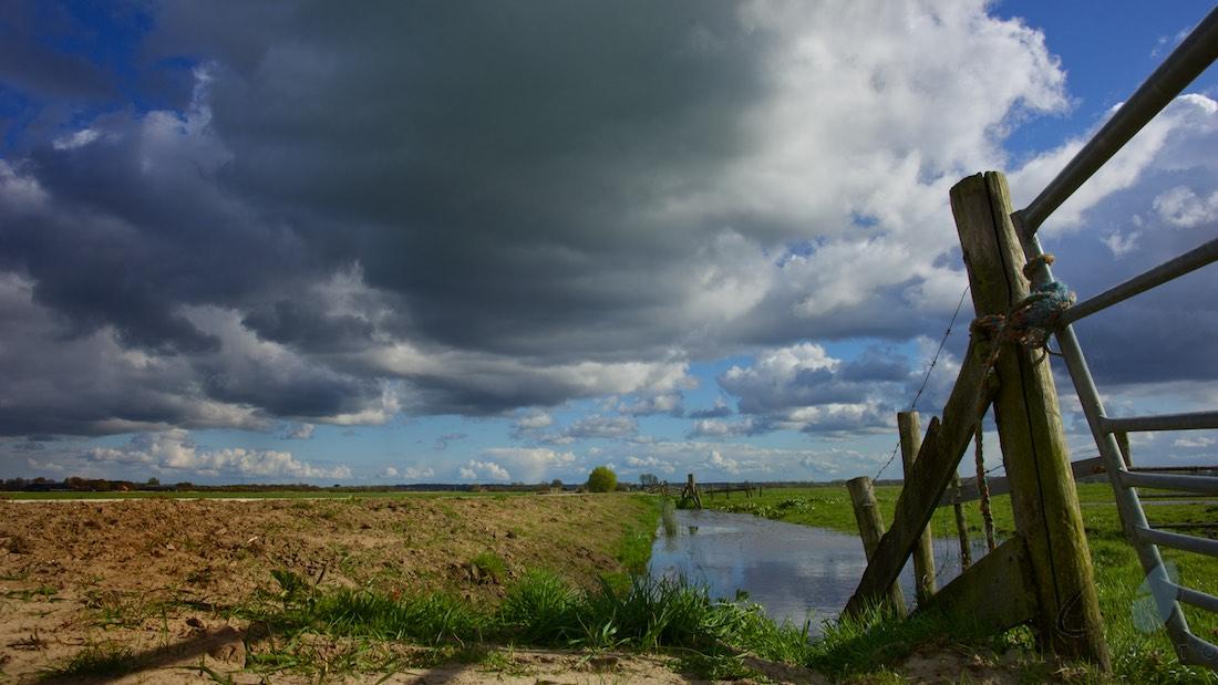 Gezichten van schoonheid. Foto van een sloot met een imposante wolkenlucht.