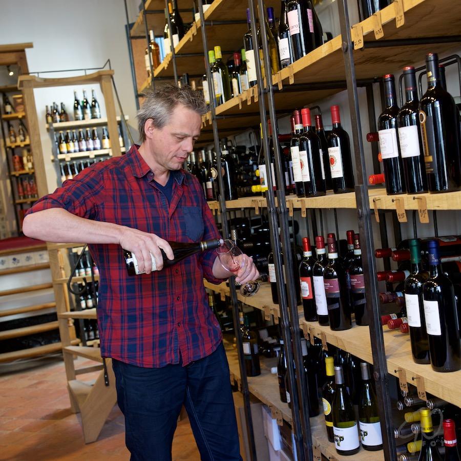 Wijn en verwonderen. Foto van een stelling in een wijnzaak. Vinoloog Klaas drupsteen schenkt een glas wijn in.