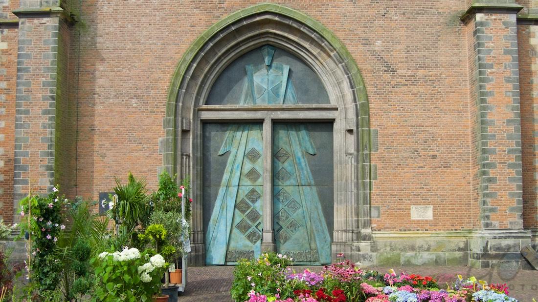 foto-expositie-in-de-onze-lieve-vrouwetoren-ruth. Foto van de bronzen toegangsdeur met beeld van Blauwe Madonna
